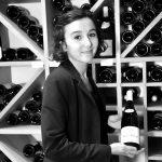 Jade Monnet, tenant une bouteille de vin